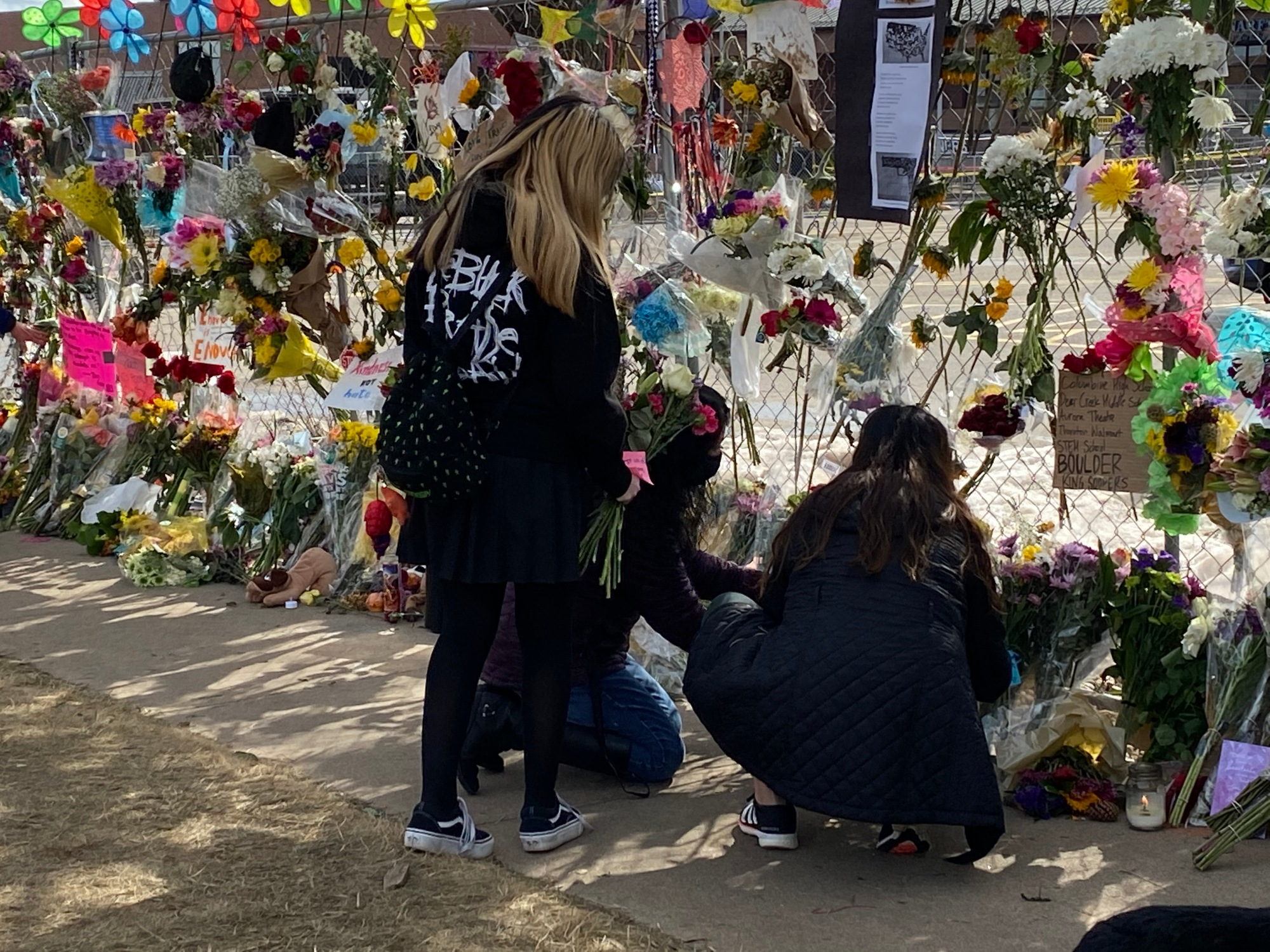 Three young women place flowers at the memorial site set up around the perimeter of the Table Mesa King Soopers parking lot.